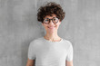 Leinwanddruck Bild - Attractive young woman in glasses standing against gray textured wall