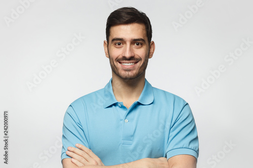 Leinwanddruck Bild Portrait of smiling handsome man in blue polo shirt, standing with crossed arms isolated on grey background
