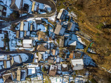 Arial view of village in swiss mountains in Ticino in winter with snow covered roofs