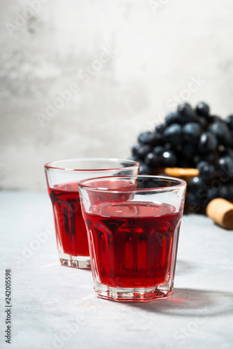 two glasses of red young wine on gray table, vertical
