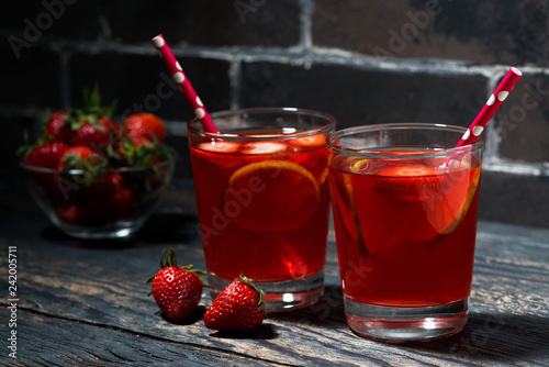 two glasses of strawberry lime lemonade on a dark wooden background - 242005711
