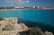 Coastline in Cyprus, rocky beach, wonderful color of sea, blue lagoon, on horizon beach, white architecture, blue sky with few clouds