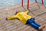 Young woman lying on a jetty and relaxing - 242010977
