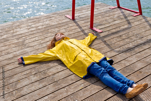 Young woman lying on a jetty and relaxing