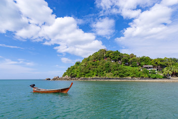 A traditional Thai longtale boat is anchored near the shore in a calm sea on a sunny day.