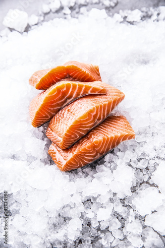 Salmon fillets portioned on ice and empty kitchen board - 242024984