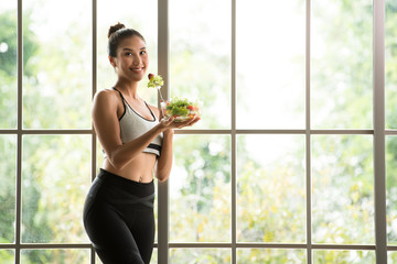 Healthy Asian woman standing and holding a salad bowl looking relaxed and comfortable © amenic181