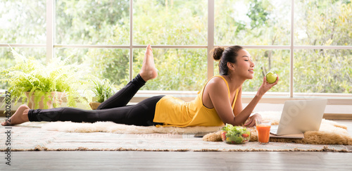 Healthy Asian woman lying on the floor eating salad looking relaxed and comfortable