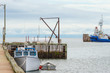 Tug boat and a fishing boat, idle for the day, no people around, hot summer day on a wharf in a New Brunswick harbour.