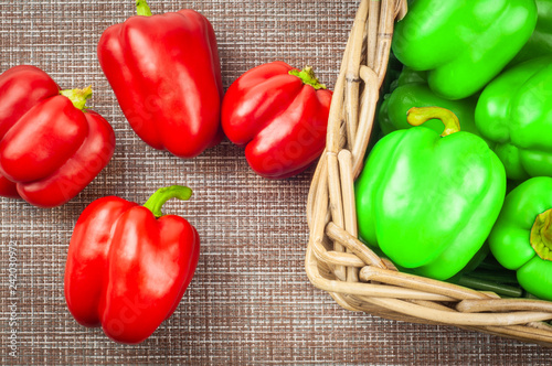 Foto Murales red and green sweet pepper in wicker basket on textile background canvas. close-up, top view