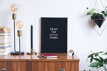 The retro mock up photo frame on the vintage wooden shelf , hanging plant in design pot, books, gold pyramid and table lamp. Concept of minimalistic shelfie.