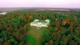 Manor in the autumn park at sunrise, Aerial view of the Kachanovo manor at sunrise, aerial view of Manor on the lake shore in autumn, manor house in autumn forest on the lake - 242038514