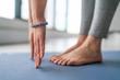 Leinwanddruck Bild - Yoga in fitness studio - yogi teacher stretching in vinyasa yoga class. Closeup of hands with blue fashion bracelet and feet.