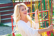 smiling blonde young elegant woman portrait  in amusement pak on flying carousel summer day