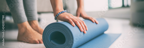 Leinwanddruck Bild Yoga at home active lifestyle woman rolling exercise mat in living room for morning meditation yoga banner background.