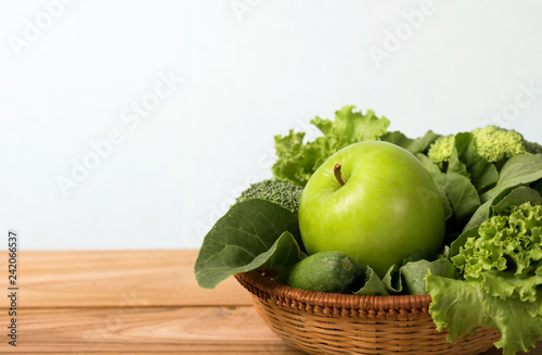 close up  green apple with mixed green vegetable  in  basket and wooden fork and spoon for healthy organic green food concept