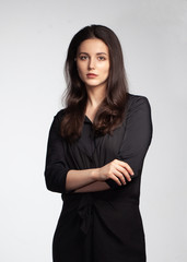 young elegance woman total black dressed with cross hands isolated on gray background © Schum