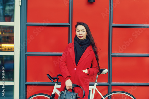 Portrait of a young Asian woman in a coat on a city street - 242084341