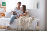 Caregiver reading book to girl with blanket while relaxing at home - 242094595
