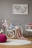 Pink pouf and flowers in grey baby's bedroom interior with poster and rocking chair. Real photo - 242094930