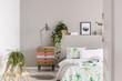 Leinwanddruck Bild - Urban jungle in grey scandinavian bedroom with wabi sabi nightstand and bed with floral duvet and blanket, real photo