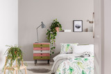 Urban jungle in grey scandinavian bedroom with wabi sabi nightstand and bed with floral duvet and blanket, real photo