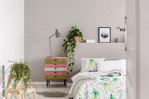 Leinwanddruck Bild Urban jungle in grey scandinavian bedroom with wabi sabi nightstand and bed with floral duvet and blanket, real photo