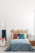 Singe bed in bright bedroom interior with copy space on empty white wall