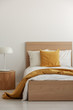Yellow pillow and blanket on white bedding in simple hotel room with single bed, copy space on empty wall