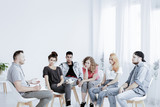 Group of teenagers during psychotherapy with professional counselor , copy space on empty white wall - 242095302