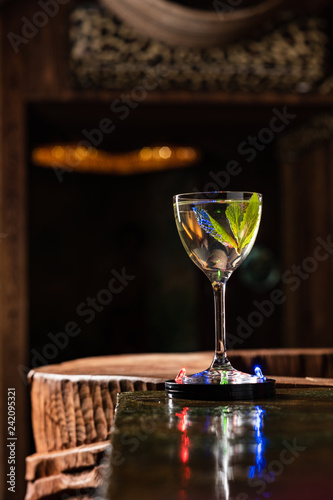 Transparent Alcoholic cocktail with mint on the bar counter