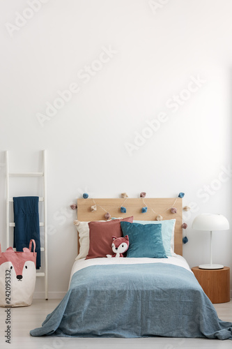 Singe bed in bright bedroom interior with copy space on empty white wall - 242095332