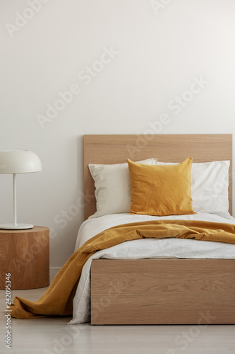 Foto Murales Yellow pillow and blanket on white bedding in simple hotel room with single bed, copy space on empty wall
