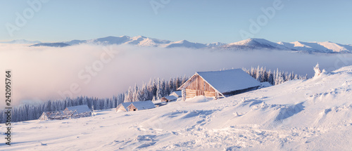 Fantastic winter landscape with wooden house in snowy mountains. Christmas holiday concept - 242095764