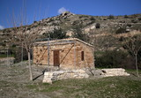 Traditional Cypriot stony house, cottage, small wall next to, trees without leaves, arid hill behind, blue sky