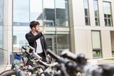 Business Mann vor dem Büro am Fahrradstand - 242105988