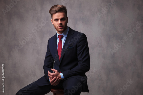 young businessman sits on wooden chair and holds hands together - 242110578