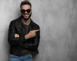 Leinwanddruck Bild - smiling casual man wearing leather jacket points to side