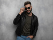 portrait of seductive relaxed man in leather jacket arranging sunglasses