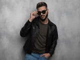 portrait of seductive relaxed man in leather jacket arranging sunglasses - 242110771