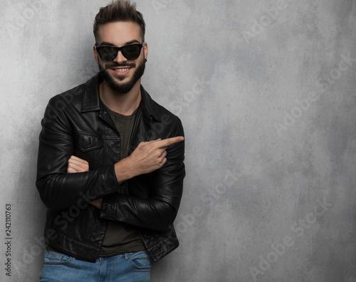 Leinwanddruck Bild smiling casual man wearing leather jacket points to side