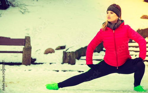Woman wearing sportswear exercising outside during winter - 242112547