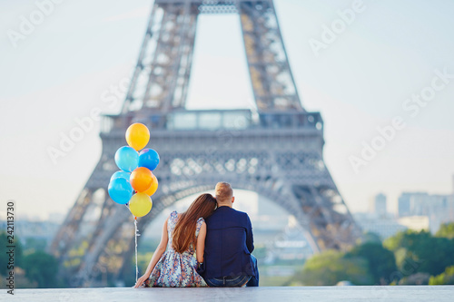 Leinwanddruck Bild Couple with colorful balloons near the Eiffel tower