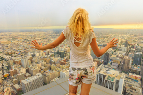Leinwandbild Motiv Aerial view of Los Angeles skyline in California, United States. Travel and tourism american concept. Blonde tourist woman looking at Downtown of LA cityscape from observation deck. Sunset shot.