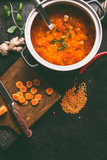 Cooking pot with tasty lentil soup and ladle on dark rustic kitchen table background with ingredients, top view with copy space. Healthy vegan food concept - 242115390