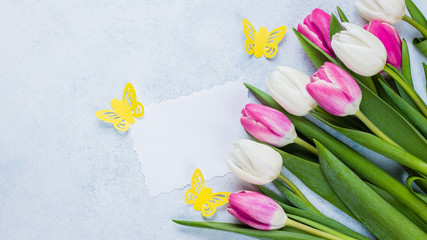 Spring Pink Tulips and Empty Paper Blank on blue stone background for Mother's Day, March 8. Easter Holiday Concept. Top view, flat lay, copy space