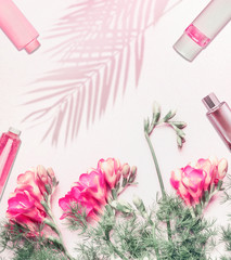 Cosmetics flat lay background with flowers and palm leaves shadow on light background, top view with copy space. Pastel color. Beauty blog concept © VICUSCHKA