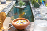 Clay bowl with scented plumeria flowers and swimming pool on the background - 242120956