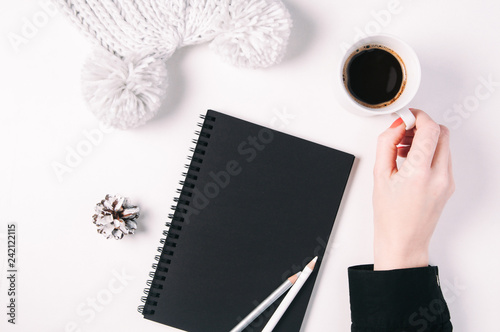 Black notebook and coffee on the table. Flat lay and top view. Template for text or design