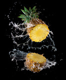 Slice of yellow pineapple with water splashing isolated on black background